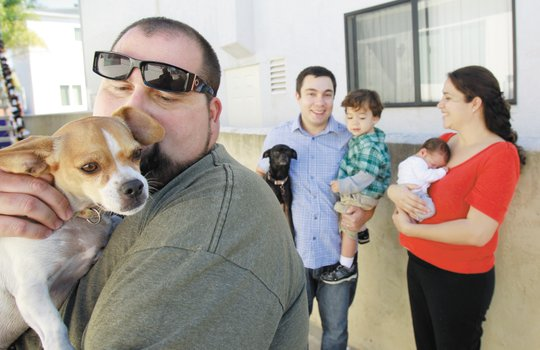 Thomas Frank, Zoe Jane, with temporary dog foster family Eamun Rahimi, holding son Michael, and Lauren Rahimi with their baby, Carter. — K.C. Alfred / U-T San Diego